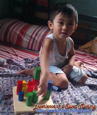 Filipino boy playing wooden toy blocks