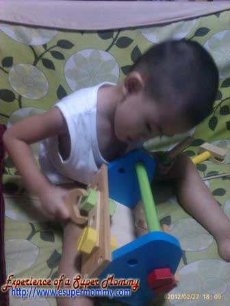 toddler playing educational wooden tool box